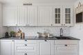 Enkelte overskap med glassfelt og belysning gir et delikat inntrykk. Kjøkkenet er utstyrt med underlimt kompositt oppvaskkum og ettgrepskran med praktisk, uttrekkbar tut. Pene fliser over laminat benkeplate.