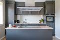 Grå kjøkkeninnredning med glassplate over heltre benkeplate. Smart kjøkkenøy med bred induksjon koketopp og takhengt ventilator med kullfilter.