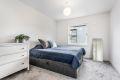 Leiligheten har et stort soverom med god plass til dobbeltseng, med tilhørende nattbord.