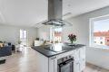 Kjøkkenøy med koketopp og oppbevaring markerer det naturlige skillet mellom kjøkken og stue.