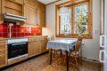 Eldre kjøkken med god skapplass og innredning med fronter i eikefinér. Integrert komfyr med koketopp og fliser over laminert benkeplate.