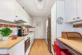 Kjøkkeninnredningen inneholder laminat benkeplate med nedfelt kum og flisfelt på vegg over benk. Opplegg for vaskemaskin