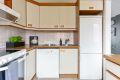 Kjøkkeninnredning med slette laminerte fronter, laminat benkeplate med fliser over, oppvaskkum, avrenningskum, kjøkkenventilator, samt frittstående komfyr, oppvaskmaskin og kjøl-/fryseskap.