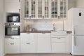 Pent og innholdsrikt kjøkken fra IKEA med integrerte hvitevarer som komfyr, induksjon platetopp og oppvaskmaskin.