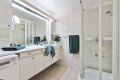 Badet består av servant med underskap, speil med overlys, veggskap, dusjkabinett og opplegg for vaskemaskin