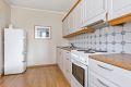 Laminat benkeplate med fliser over, dobbel oppvaskkum, kjøkkenventilator antatt med kullfilter, samt frittstående komfyr og kjøl-/fryseskap. Alle hvitevarer på kjøkkenet medfølger boligen ved salg.