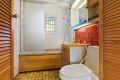 Eldre bad/wc består av frittstående wc, servant med underskap, speil med overlys, veggskap, samt badekar med dusjgarnity og glassvegg mot innredning