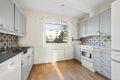 Kjøkkeninnredning med malte profilerte fronter, laminat benkeplate med fliser over, dobbel oppvaskkum med benkebeslag, kjøkkenventilator med kanal ut, samt frittstående komfyr, oppvaskmaskin og kjøl-/fryseskap.