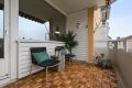 Stor, solrik balkong med markise, uteblysning og trelemmer på gulv.