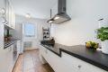 Pent kjøkkent med integrert hvitevarer og frittstående kjøleskap. God skap- og benkeplass.