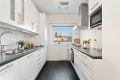 Pent kjøkken med integrerte hvitevarer; oppvaskmaskin, kjøl-/fryseskap, komfyr, koketopp og mikro.