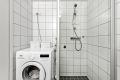 Veggmontert dusj med dusjvegger og opplegg for vaskemaskin.