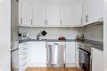 Kjøkkeninnredning med glatte fronter og fliser over benkeskap. Opplegg for oppvaskmaskin.