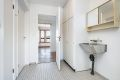 Vaskerom med originale fliser på gulv, malte vegger og malt tak. Innredningen består av tørkeskap, utslagsvask og opplegg for vaskemaskin.