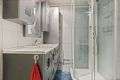 Innredningen består av vegghengt wc, heldekkende servant med underskap, speil med sideskap, langskap, dusjkabinett og varmekabler i gulv.