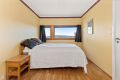 Soverom 1 med parkett på gulv, malte strier på vegger og malt tak. Rommet har en paktisk plassbygd skyvedørsgarderobe og inngang til en romslig innvendig bod.