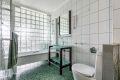 Bad med stilig innredning og mosaikkfliser på gulv.