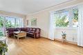 Lys og romslig stue med vinduer på flere vegger som slipper inn rikelig med naturlig lys