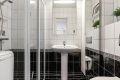 Flislagt bad/wc med eget dusjhjørne. Praktisk høyskap med speilfront og hyller gir gode lagringsmuligheter for toalettartikler, mm.
