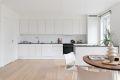 Pent og moderne kjøkken med laminat benkeplate og slette lakkerte fronter
