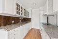 Kjøkken med profilert innredning, laminat benkeplate og fliser over kjøkkenbenk.