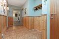 Romslig entré med belegg på gulv, brystningspanel på vegger med tekstilstrier over, malt tak.