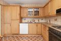 Godt utnyttet kjøkkeninnredning med profilerte eikefronter, laminat benkeplate med fliser over, ventilator, integrert komfyr med koketopp og opplegg for oppvaskmaskin.