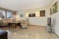 Romslig stue med laminat på gulv, malte strier på vegger og malt tak.