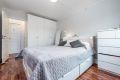 Soverom 1 med laminat på gulv, malte strier på vegger og malt tak. Plassbygd garderobeskap.