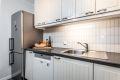Kjøkkeninnredning med profilerte lakkerte formpressede fronter, laminat benkeplate, veggplater med flis-mønster over benkeplate, ventilator og opplegg for oppvaskmaskin.
