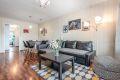 Stue med laminat på gulv, malt tapet og malt trepanel på vegger, malt tak.