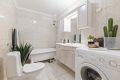 Romslig flislagt bad med varmekabler. Opplegg for vaskemaskin.