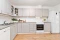 Kjøkkenet er malt i en lun gråfarge og innredningen er fra byggeår