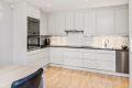 Kjøkkenet har hvite slette fronter med godt med skap- og skuffeplass