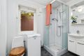 Badet er ustyrt med dusjkabinett, toalett og servant