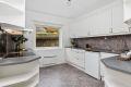 Kjøkkenet har hvit profilert innredning med integrert komfyr og steketopp