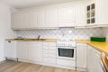 Kjøkkenet er hvitmalt og fremstår som velholdt