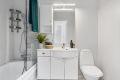 Badet har badekar, baderomsinnredning med overskap og gulvmontert wc