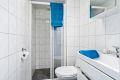 Badet er innredet med klosett, servant på innredning, speilskap og dusjnisje.