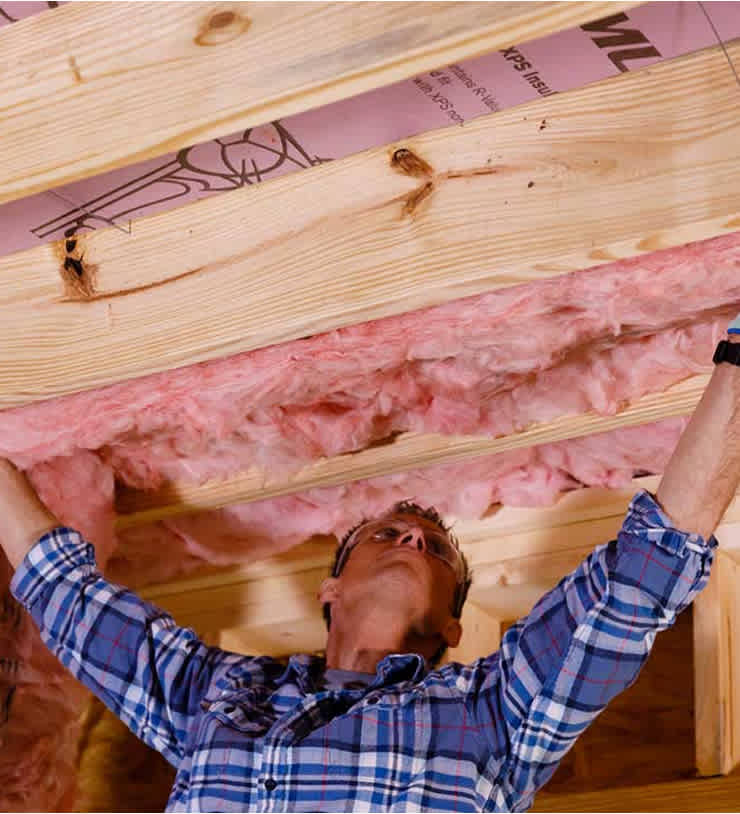 photo of man hanging insulation