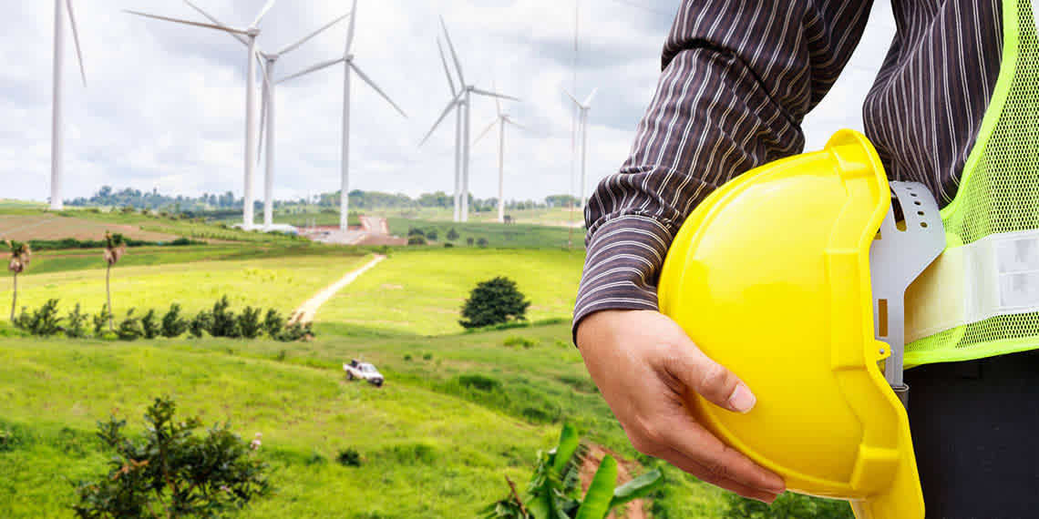 photo of wind turbines with a worker in the foreground