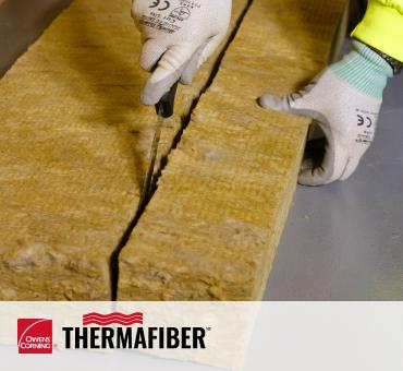 Travailleur coupant l'isolation en laine minérale