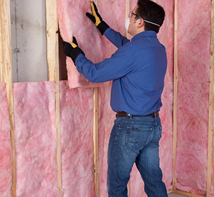 worker installing insulation in a basement