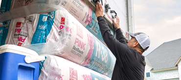 Worker stacking packaged insulation