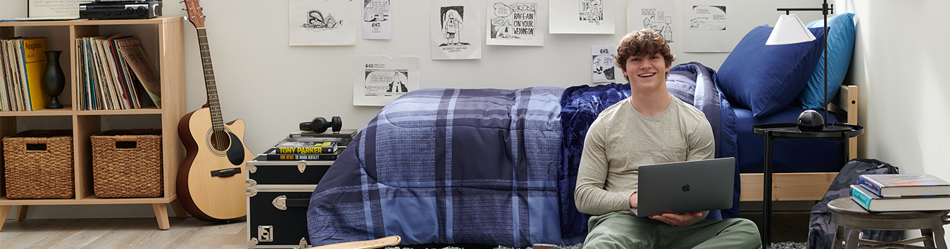 Student on his dorm with laptop