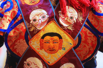 """Decorations on the robe of a mask dancer at the annual Paro Tshechu (religious festival) at Paro's Rinpung Dzong (a Buddhist monastery and fortress). The Paro Tshechu is the most popular religious dance festival in Bhutan held annually since the 17th century. It lasts 5 days beginning on the 10th day of the 2nd Bhutanese lunar month. Paro (Dzongkha) is an ancient town in the homonymous valley, with many sacred sites, temples and historical buildings. The Kingdom of Bhutan is landlocked in the Eastern Himalayas. The Head of state is the King of Bhutan, known as the """"Dragon King"""". Never colonized, the Kingdom sits on the ancient Silk Road between Tibet, Indian and Southeast Asia. Bhutan is famous for pioneering the concept of Gross National Happiness."""