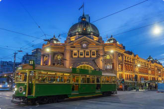 Tram passing Flinders Street Station at dusk