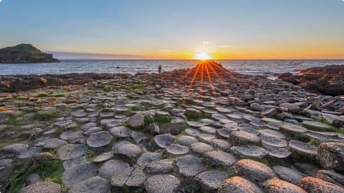 Tourist at Sunset over Giants Causeway, Northern Ireland