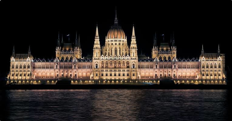 A view of the Hungarian Parliament Building at night in Budapest