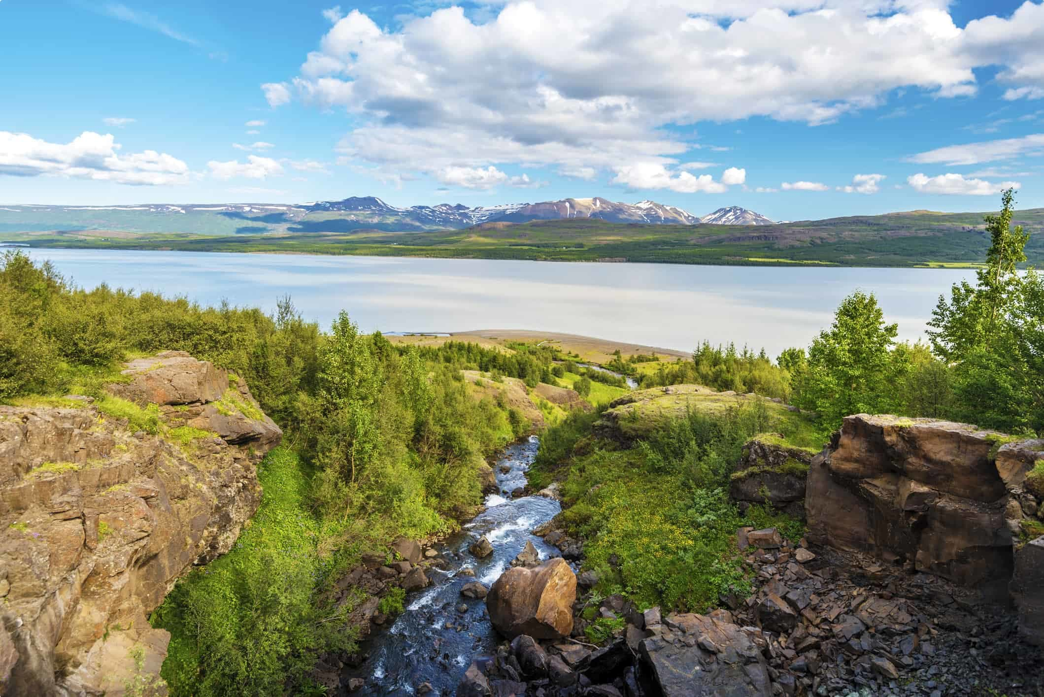 Water course falling down to Lagarfljot lake in Eastern Iceland, the mountain landscape of Fljotsdalsherad municipality is at background